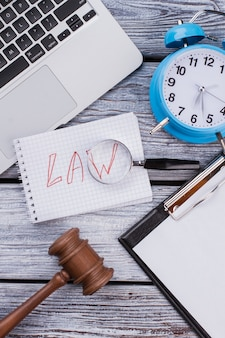 Concepto de ley y tiempo. portátil con portapapeles y martillo sobre mesa de madera blanca.