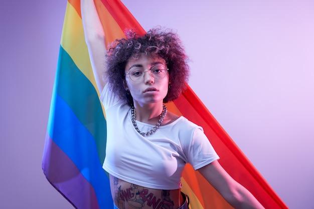 Concepto lgbtq. chica caucásica positiva con pelo rizado afro sosteniendo la bandera del arco iris aislado en estudio