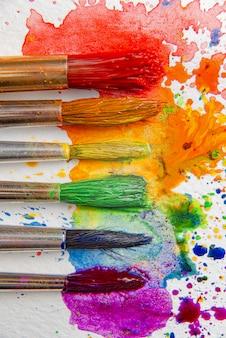 Concepto lgbtq de colores hechos con la ayuda de pinturas de acuarela y pinceles de flores de azalea en una hoja de papel para pintar con acuarela