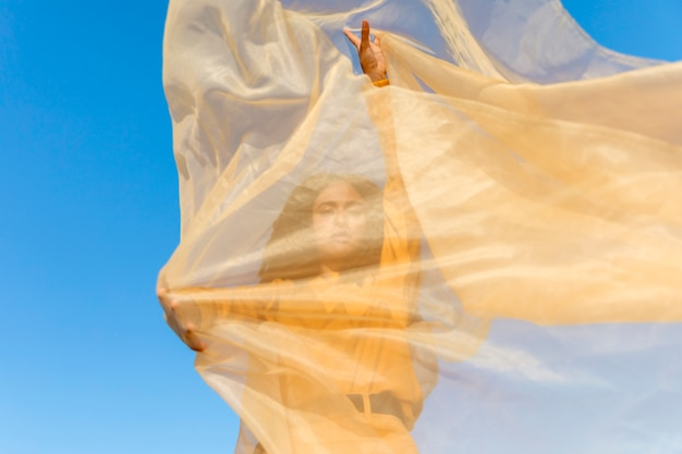 Concepto de libertad con mujer sujetando tela en la naturaleza