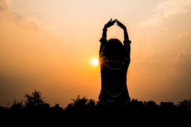 Concepto de libertad de las personas concepto: silueta de una mujer joven asiática que se relaja, confianza fuerte abre los brazos y mira la escena de la puesta de sol en el cielo de la puesta del sol del verano outdoo