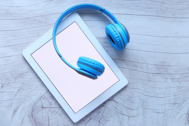 Concepto de libro de audio. auriculares y tableta digital en mesa