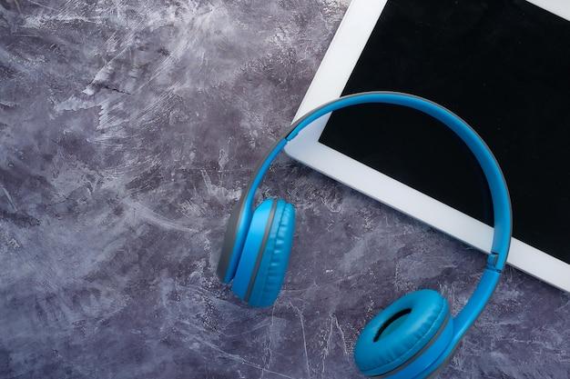 El concepto de libro de audio, auriculares y tableta digital sobre fondo negro