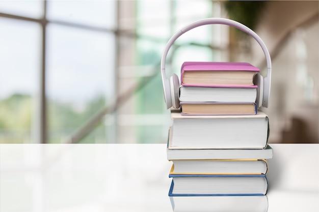 Concepto de libro de audio, libros y auriculares en el fondo