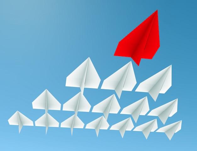 Concepto de liderazgo. un avión líder rojo lleva a otros aviones blancos hacia adelante.