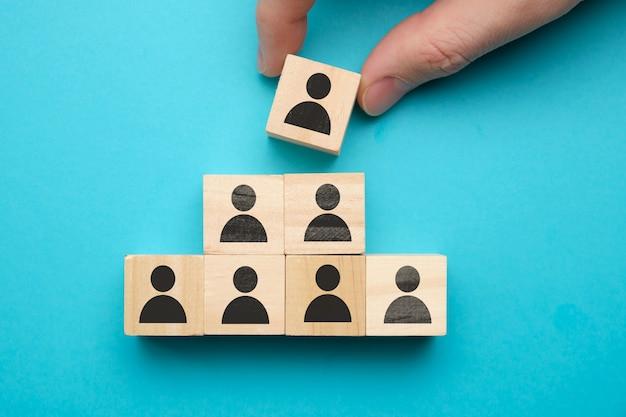 Concepto de liderazgo - bloques de madera con personas abstractas en un espacio azul.