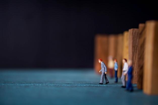 Concepto de liderazgo. figura miniatura del empresario que lidera desde otro.