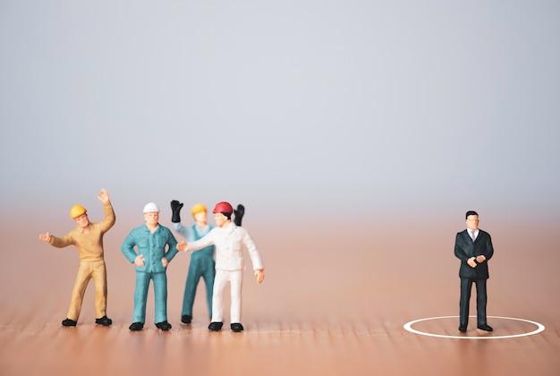 Concepto de liderazgo y pensamiento diferente, gerente de figura en miniatura separado de los trabajadores del personal.