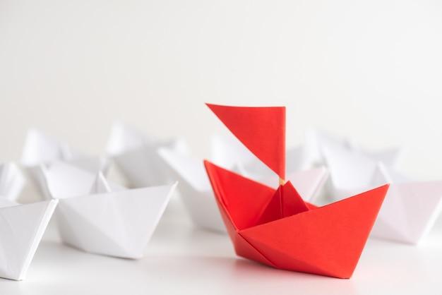 Concepto de liderazgo plomo de la nave de papel rojo entre blanco.