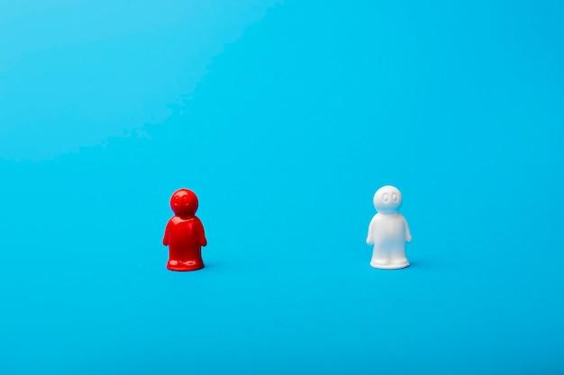 Concepto de liderazgo sobre un fondo azul, figuras de hombres, una figura roja sirve como líder. negocios y trabajo en equipo social, logrando el éxito, la autorrealización. establecerse como líder de la industria