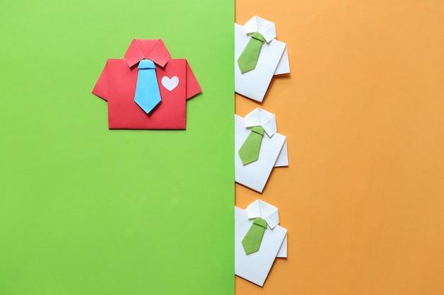 Concepto de liderazgo y trabajo en equipo, camisa roja de origami con corbata y líder entre una pequeña camisa amarilla