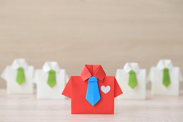 Concepto de liderazgo y trabajo en equipo, camisa roja de origami con corbata y líder entre pequeñas camisas en blanco