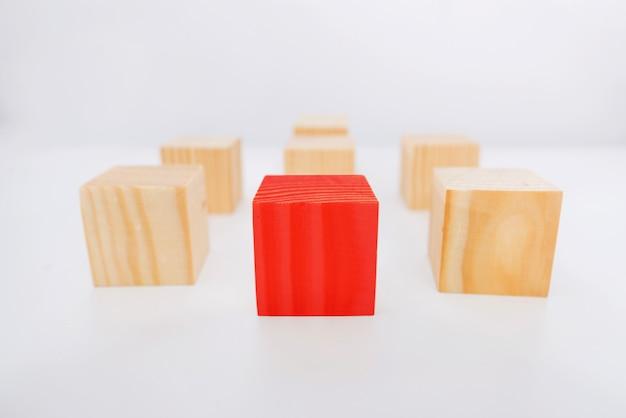 Concepto de liderazgo utilizando un cubo rojo entre muchos otros cubos.