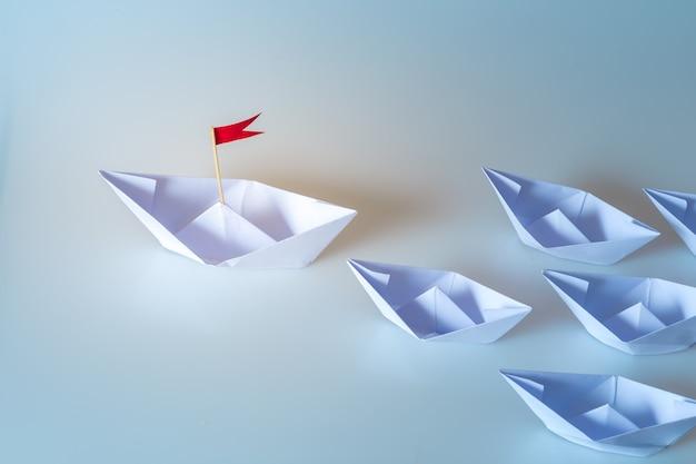 Concepto de liderazgo utilizando papel nave con bandera roja sobre fondo azul