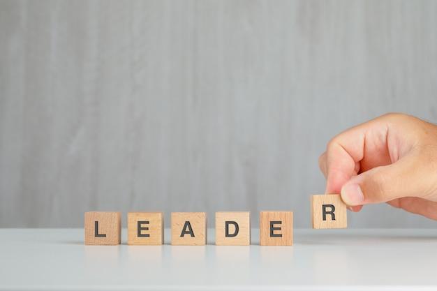Concepto de liderazgo en vista lateral de la mesa gris y blanco. mano recogiendo cubo de madera.