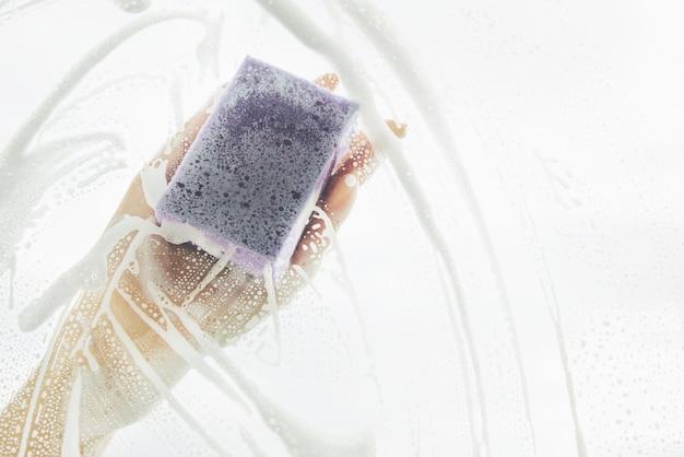 Concepto de limpieza - cristal de ventana de limpieza a mano con detergente. copia espacio