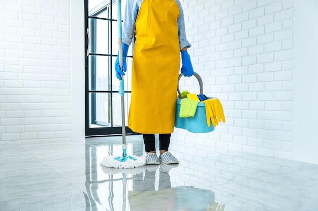 Concepto de limpieza y limpieza, mujer joven feliz en guantes de goma azul limpiando el polvo con un trapeador mientras limpia en el piso en casa