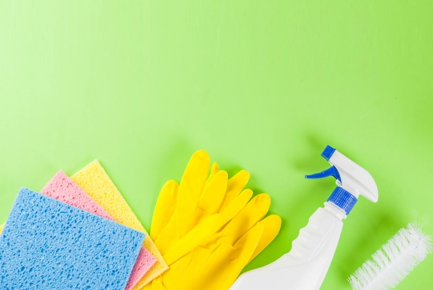 Concepto de limpieza de primavera con suministros, productos de limpieza de la casa de la pila. concepto de tarea doméstica, en el espacio de copia de vista superior de fondo verde