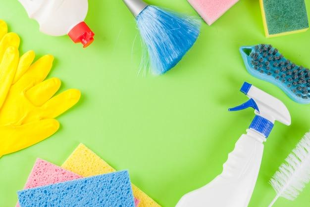 Concepto de limpieza de primavera con suministros, productos de limpieza de la casa de la pila. concepto de tarea doméstica, sobre fondo verde vista superior copia espacio marco
