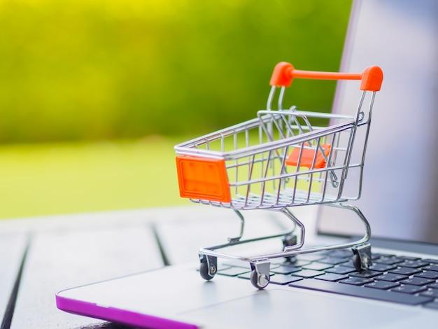 Concepto en línea de compras: mini carro de compras en la computadora portátil.