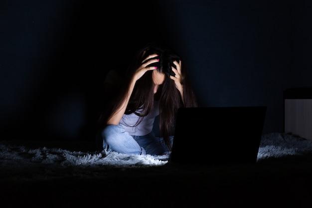 Concepto en línea de intimidación. sola niña preocupada sentada en su casa en la cama con teléfono móvil y portátil.