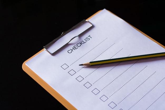 Concepto de lista de verificación: lista de verificación, papel y un bolígrafo con palabra de lista de verificación en la mesa de madera