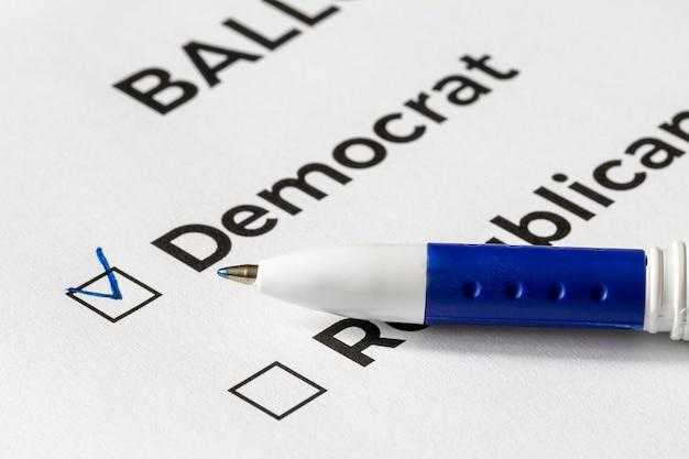 Concepto de lista de verificación primer plano de la papeleta con las palabras demócrata y republicano y una pluma en él. una marca de verificación para demócrata en la casilla de verificación.