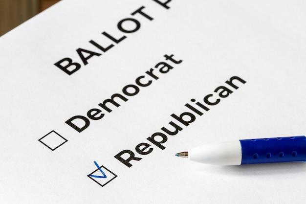 Concepto de lista de verificación primer plano de la papeleta con las palabras demócrata y republicano y una pluma en él. una marca de verificación para republicano en la casilla de verificación.