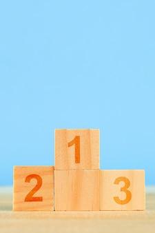 Concepto de logro podio de madera de pie en azul.