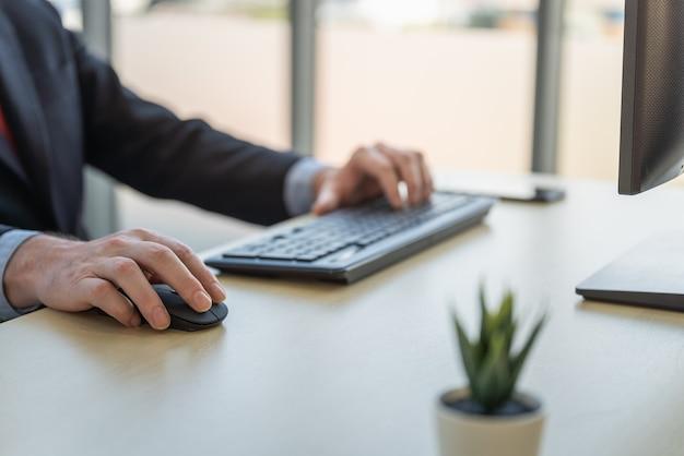 Concepto de lugar de trabajo, tecnología y negocios. primer plano de una computadora de escritorio de trabajo de mano de empresario caucásico con ratón y teclado