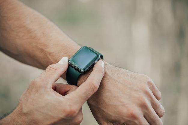 Concepto macro de hombre haciendo clic, apuntando en una pantalla de su reloj inteligente de diseño genérico