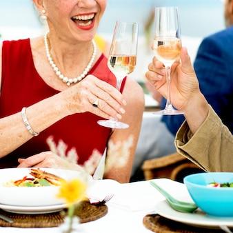 Concepto maduro de los amigos que cenan fino al aire libre