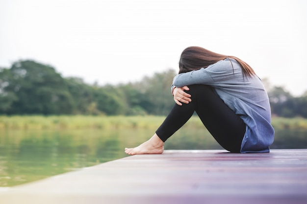 Concepto de mal día. tristeza mujer sentada junto al río en la terraza del patio de madera