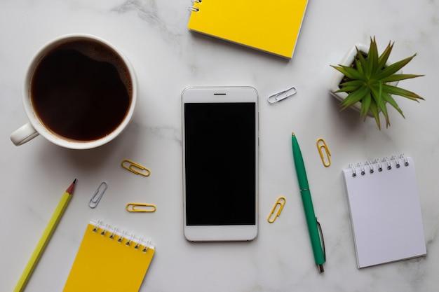 Concepto de mañana, comienzo del trabajo. lugar de trabajo con blocs de notas, teléfono inteligente, café, lápiz, bolígrafo y planta