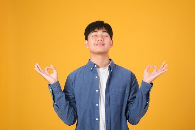 Concepto de manejo del estrés. hombre joven pacífico meditando, encontrando armonía y equilibrio interior