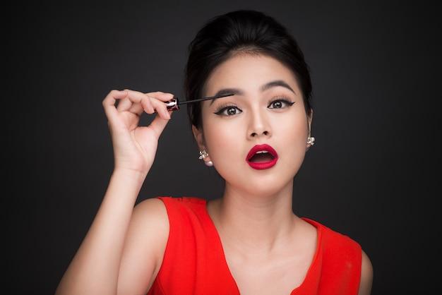 Concepto de maquillaje y cosmética. mujer asiática haciendo su rímel de pestañas de maquillaje negro.