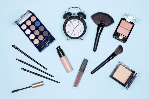 Concepto de maquillaje rápido de 5 minutos. reloj despertador con productos y accesorios esenciales de maquillaje, plano