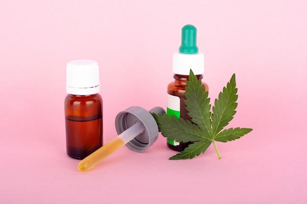 Concepto de marihuana medicinal, hoja de cannabis y pipeta con extracto de concentrado de thc psicoactivo sobre fondo rosa.