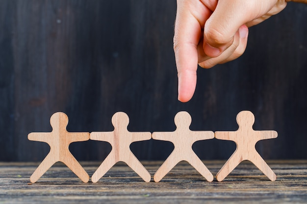 Concepto de marketing y análisis de clientes en vista lateral de fondo de madera y grunge. dedo apuntando al hombre de madera.
