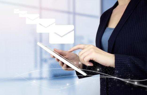 Concepto de marketing por correo electrónico. envío de newsletter. tableta blanca táctil de mano con holograma digital signo de correo electrónico y sms sobre fondo borroso claro. envío de correo electrónico correo masivo.