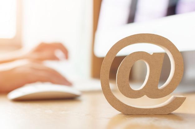 Concepto de marketing por correo electrónico, mano mediante computadora que envía un mensaje con símbolo de dirección de correo electrónico de madera
