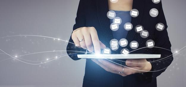 Concepto de marketing por correo electrónico y sms. tableta blanca en la mano de la empresaria con signo de holograma digital sobre fondo gris. empresa que envía muchos correos electrónicos o boletines digitales a los clientes.