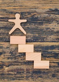 Concepto de marketing con figura de madera y bloques sobre fondo de madera plana lay.