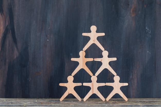 Concepto de marketing y gestión de clientes con figuras de madera en vista lateral de fondo de madera y grunge.