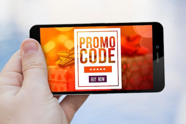 Concepto de marketing móvil: mano sosteniendo un vale de regalo en la pantalla del teléfono inteligente