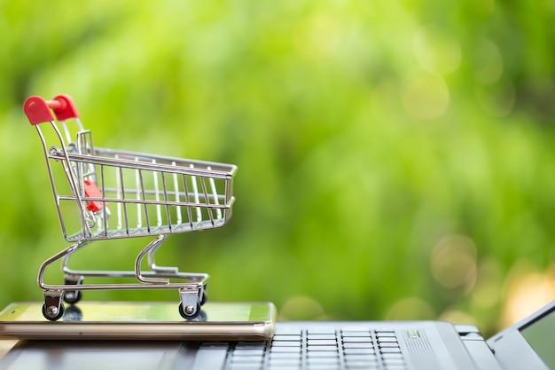 Concepto de marketing y pago en línea: carro de compras con teléfono inteligente en la computadora portátil e icono de compras en línea y redes sociales.