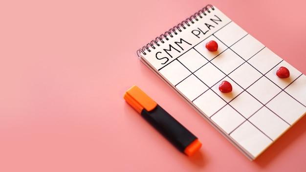 Concepto de marketing en redes sociales: plan smm en un cuaderno sobre un fondo rosa con dulces en forma de corazones