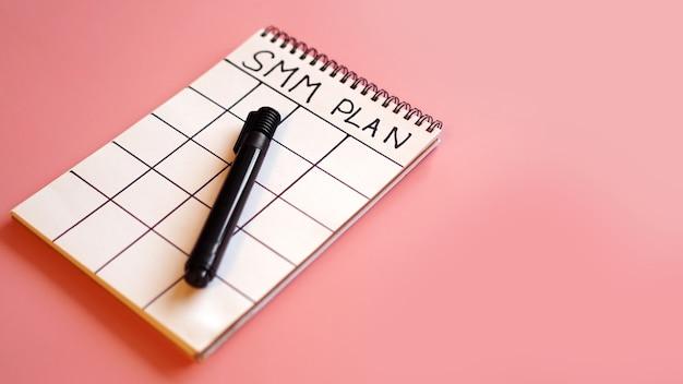Concepto de marketing en redes sociales - plan smm en un cuaderno sobre un fondo rosa