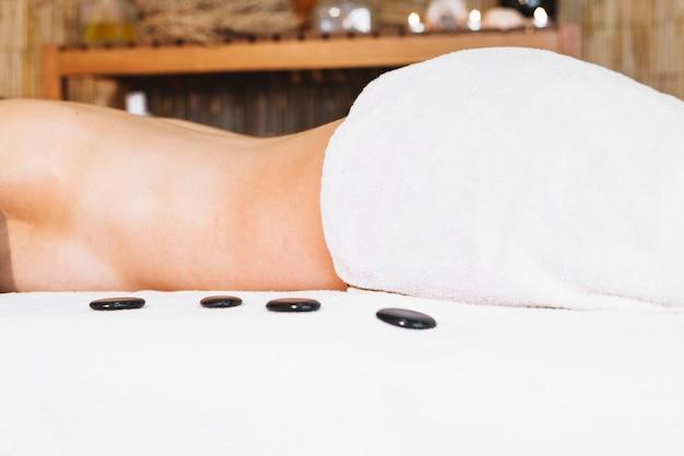 Concepto de masaje con piedras al lado de mujer