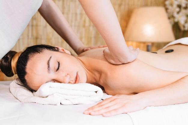 Concepto de masaje con piedras en espalda de mujer